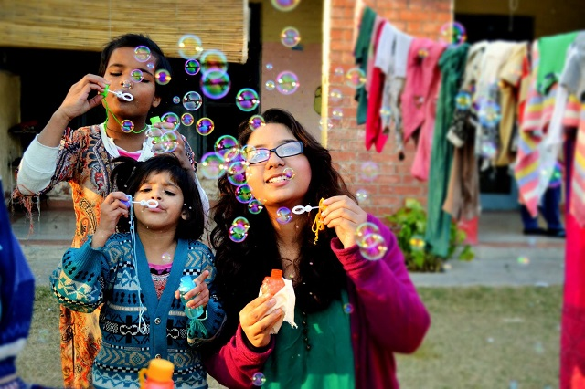 SOS children blowing bubbles at a village in Pakistan.