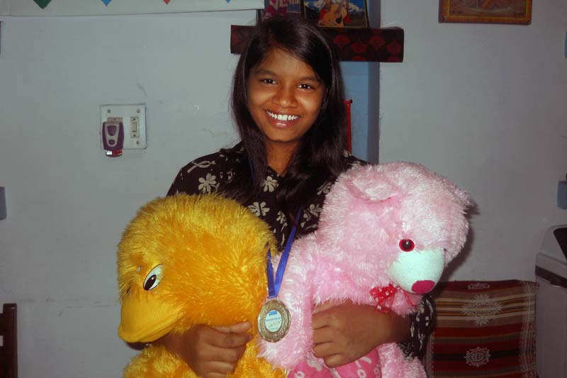 Girl with medal and teddy bears in India