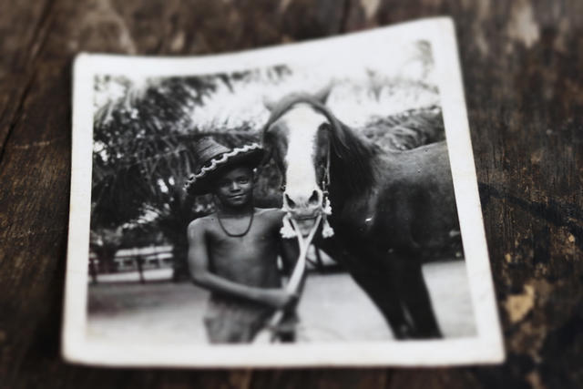 Black and white photo of Raphael Adou as a child, standing next to a horse.