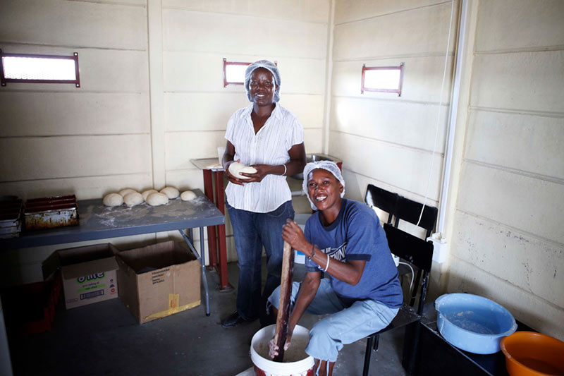 Mothers part of the Ondangwa Family Strengthening Program baking bread in Namibia