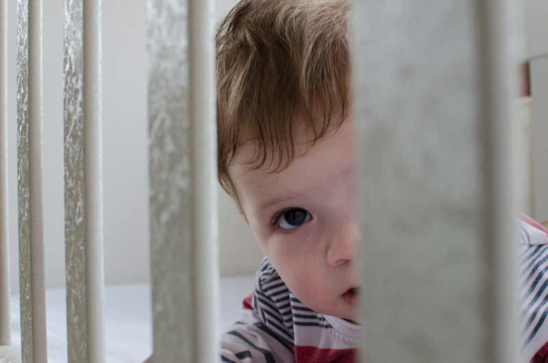 Sponsored boy looking through crib in Kosovo