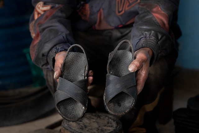 Secundino showing the custom footwear he produces.