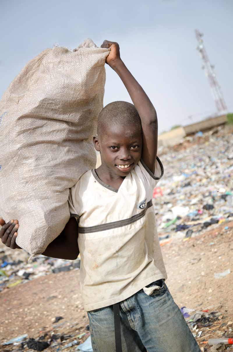 Child labour - Boy holding bag of grain
