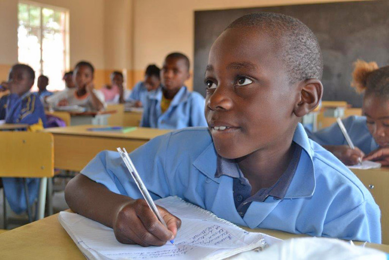 Boy writing at his desk at the SOS School in Buambo, Angola