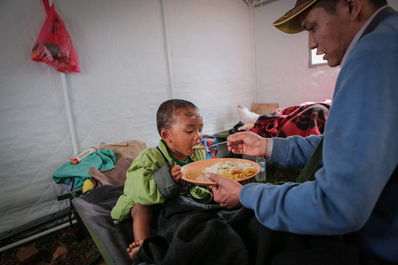Young boy being fed at relief camp after Nepal earthquake