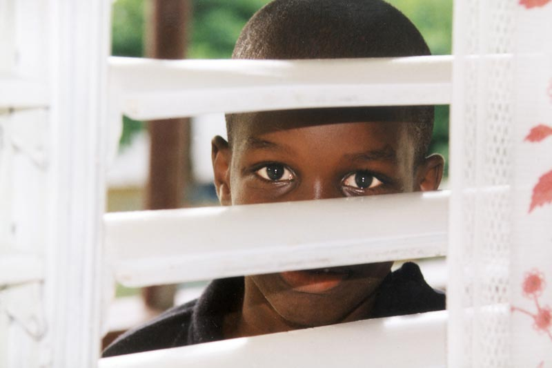 Boy looking through blinds - Sponsor a child in Jamaica
