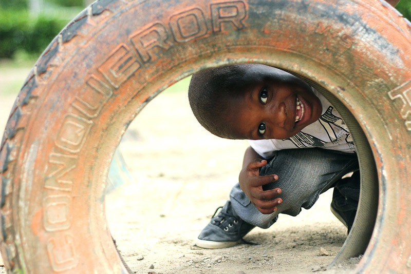 Sponsored boy looking through a tire - Sponsor a child in Dominican Republic