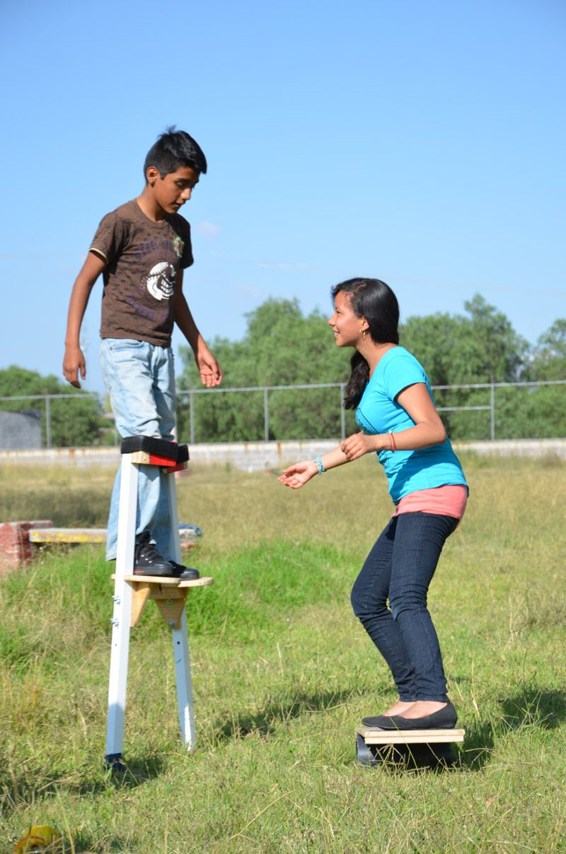 Boy on stilts and girl on balance board as part of the SOS Social Circus Program in Mexico