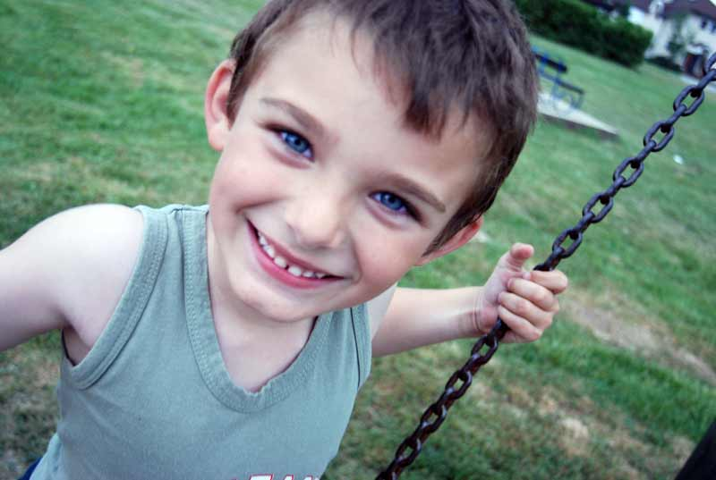 Boy smiling on a swing - Sponsor a child in Croatia