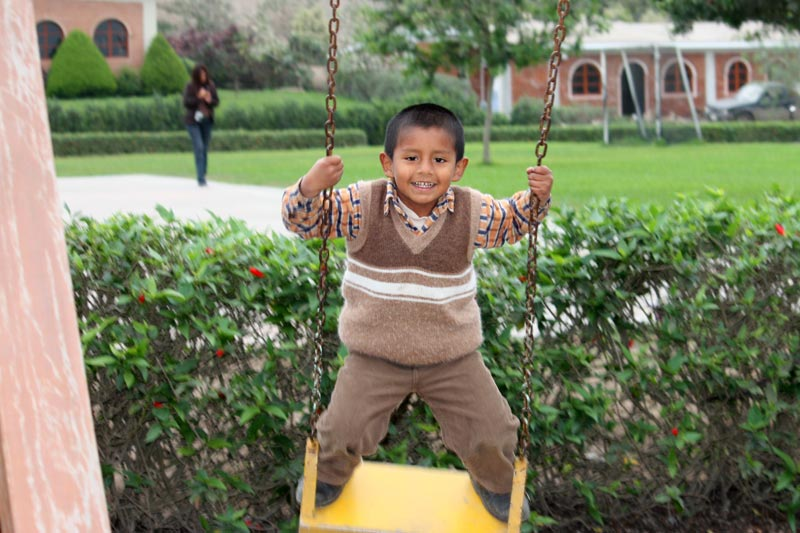 Boy on swing - Sponsor a child in Peru