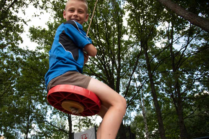 Smiling boy on swing at summer camp in Belarus