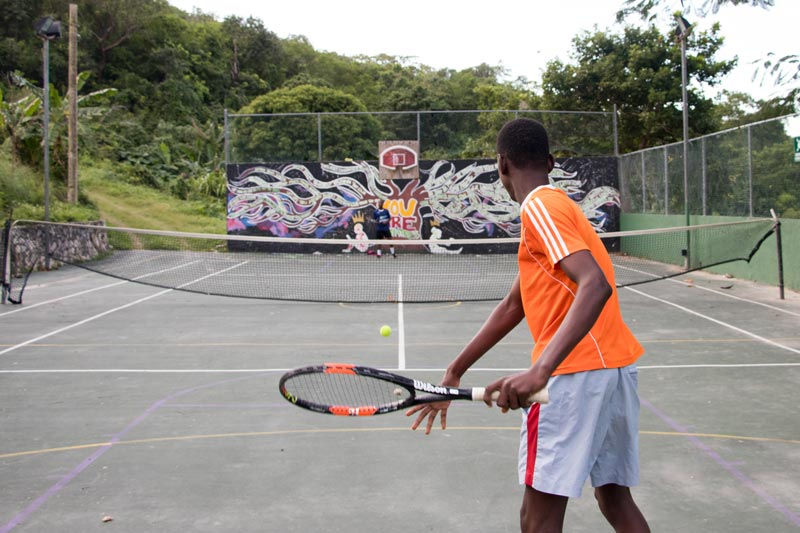 Boy playing tennis in Barrett Town, Jamaica