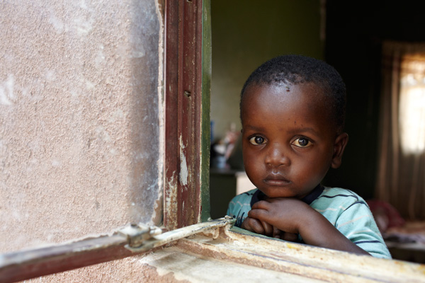 Child looking through window in Tlokweng, Botswana