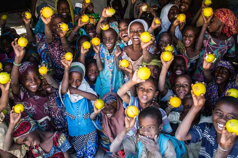Children holding up oranges - Diffa, Niger