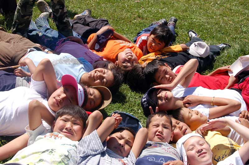 Sponsored children lying on the grass in Kyrgyzstan
