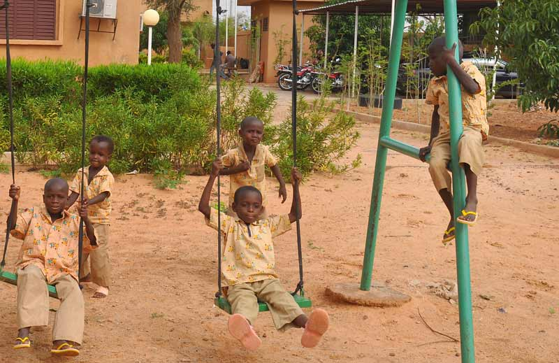 Sponsored children in NIger playing on swing set