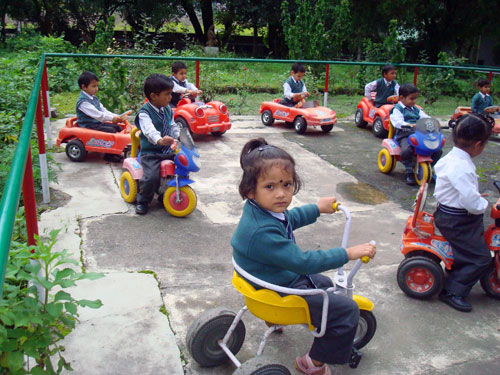 Children on tricycles in Bhimtal, India