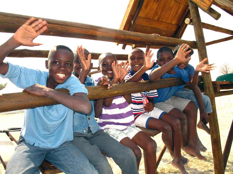 Children waving from a play structure in Ondangwa, Namibia