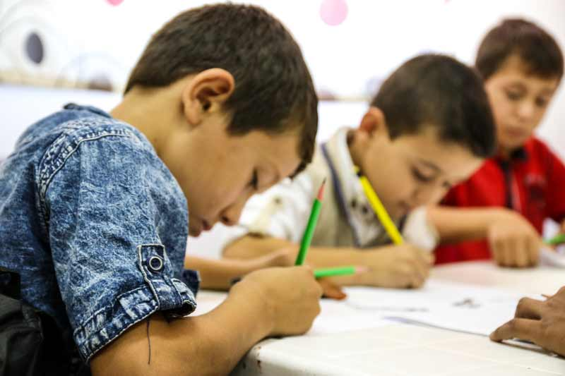 Syrian and Jordanian children working on their studies