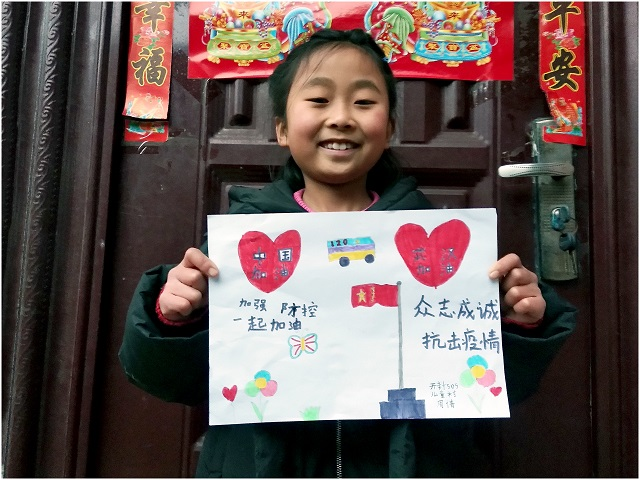 An SOS child shows off a homemade newspaper about the coronavirus outbreak.