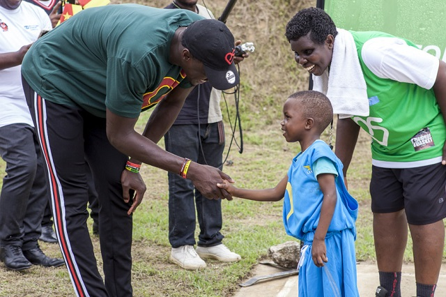 """""""Giant"""" Pascal Siakam shakes hands with a young SOS child."""