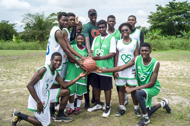 Pascal Siakam and local Camaroon youth pose with a basketball.