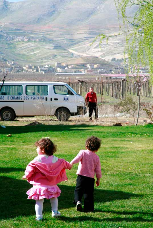 A boy and girl walking to the school bus in Lebanon