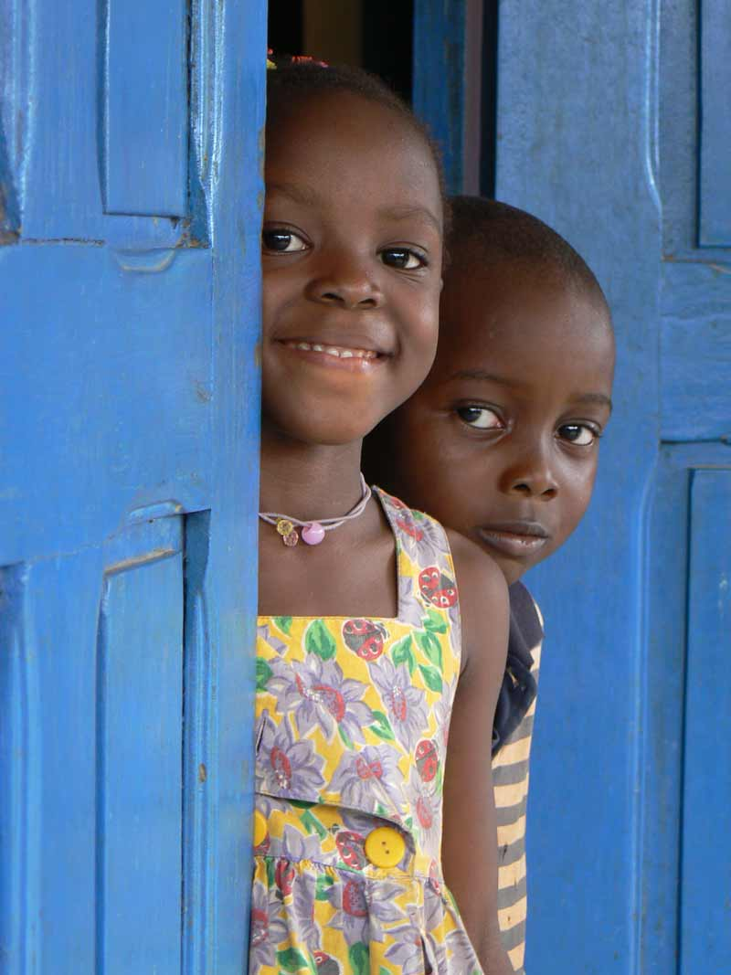 Girl and boy looking out doorway in Guinea