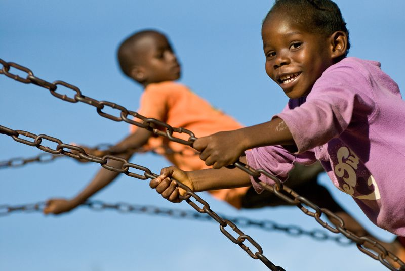 Two sponsored children playing on swings in Liberia