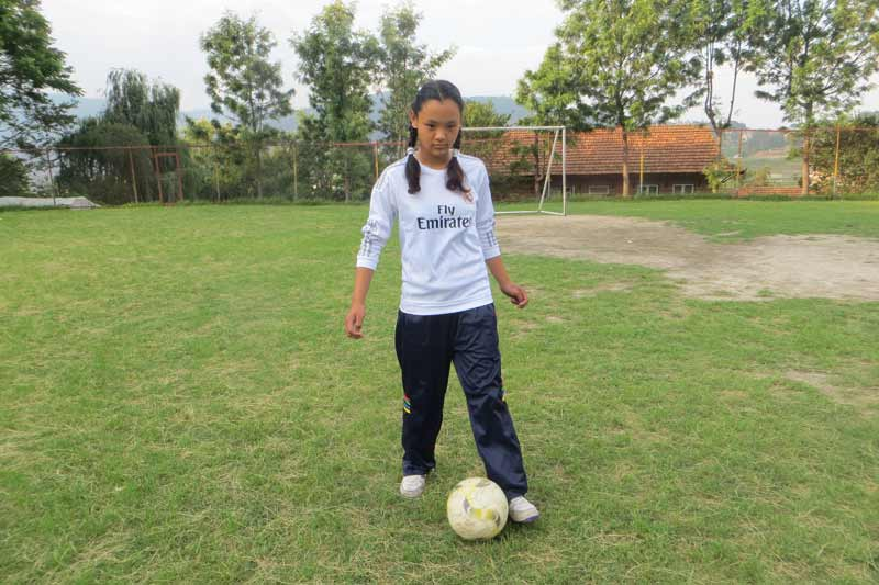 Girl playing soccer in Nepal