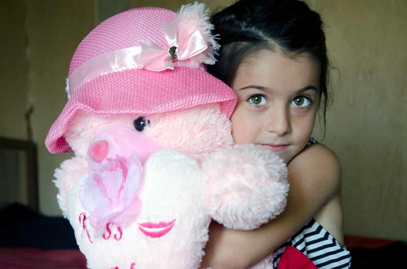 Girl holding stuffed teddy bear in Georgia - Sponsor a child in Georgia