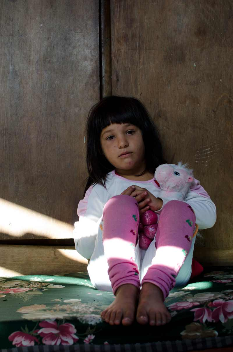 Girl sitting in dark with stuffed animal
