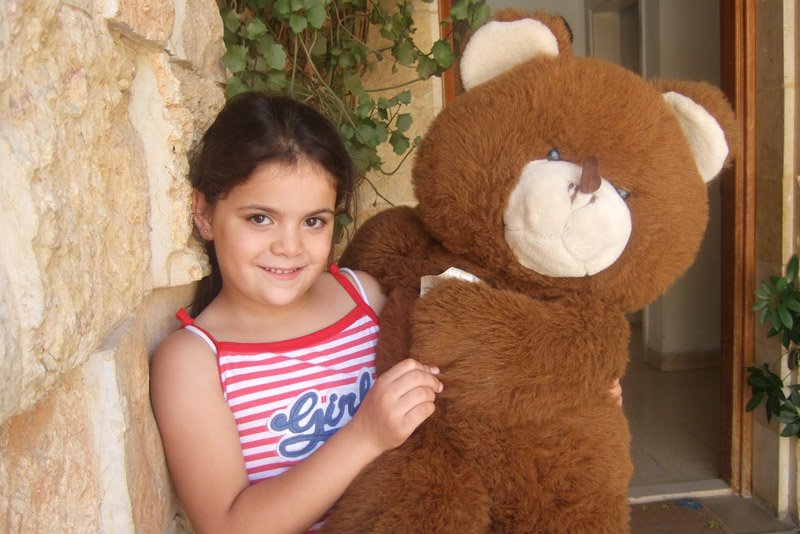 Jordanian sponsored girl holding a big teddy bear in Irbid, Jordan