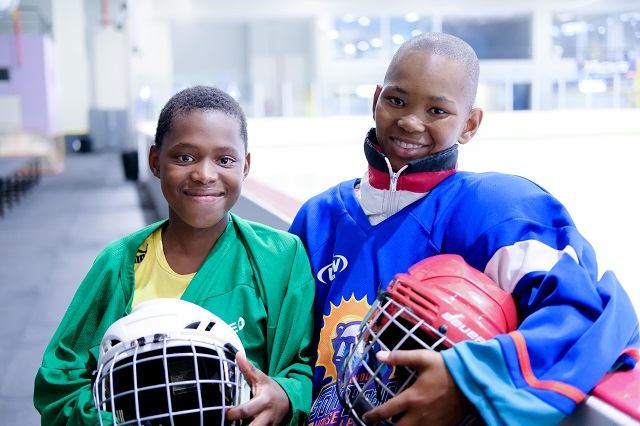 Khaya* and Pieter* smiling in their hockey gear