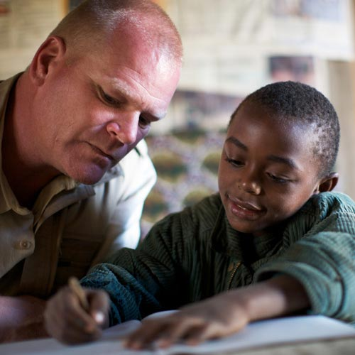Mike Holmes helping a child with their homework for charity