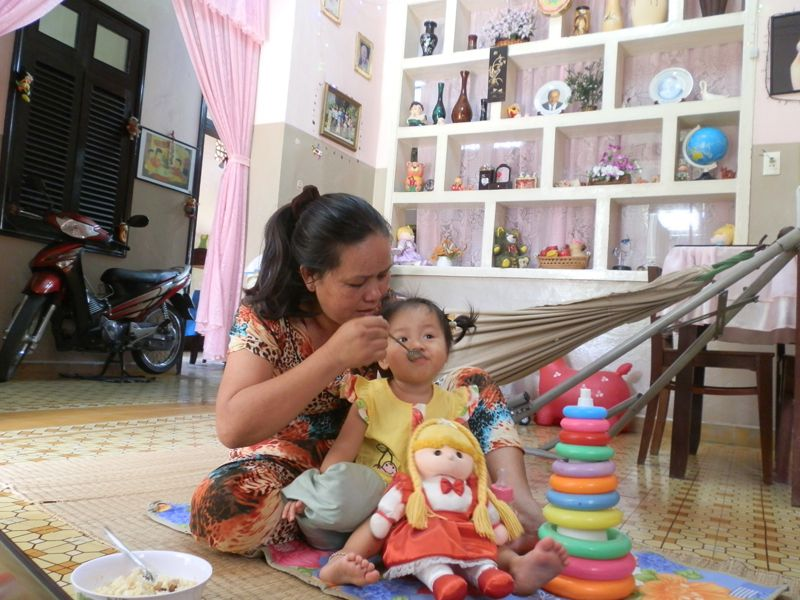 Mother feeding SOS child with toys in Go Vap, Vietnam