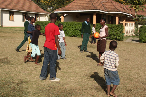Neema playing soccer with children in Tanzania