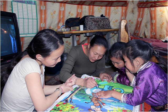 Arban* and her sister working on their studies, with help from mom.