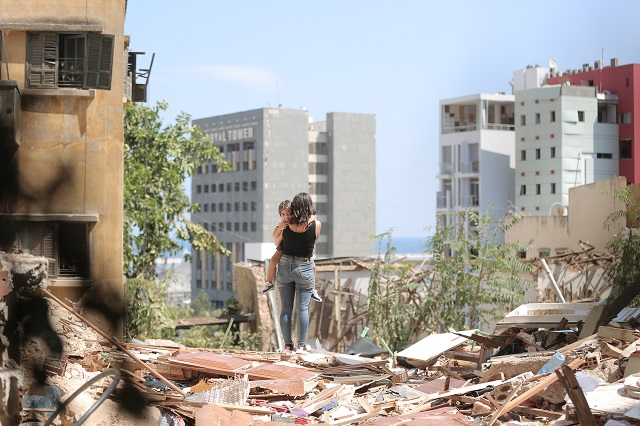 A mother and daughter walk through the debris of their apartment complex