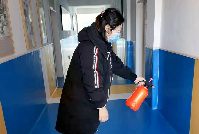 A woman disinfects an SOS school.