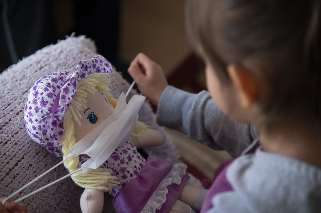 A child puts a protective mask on her toy.
