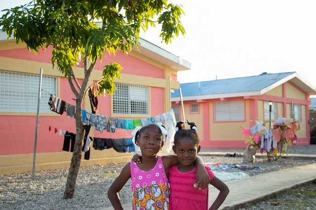 Two smiling SOS children standing in front of their new SOS home.