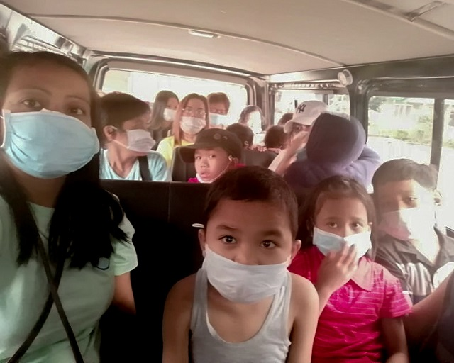 SOS children wear protective masks as they evacuate.