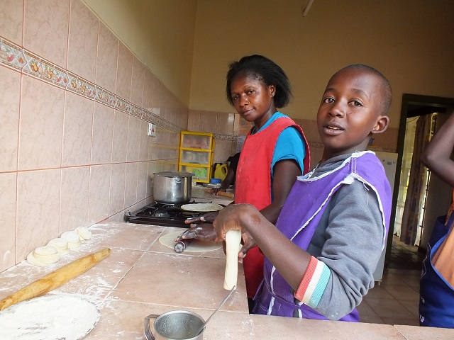 Rodah and her SOS Children baking in the kitchen.