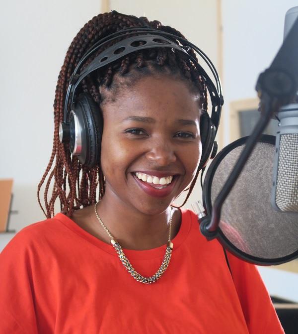 Tumi smiling in the recording studio.