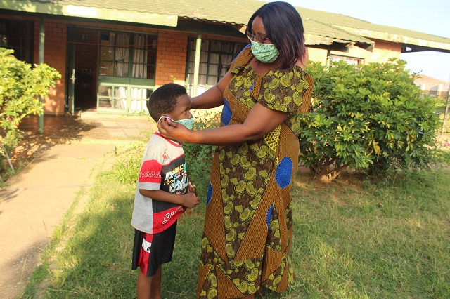 SOS mother Phoebe helps her youngest put on a protective mask