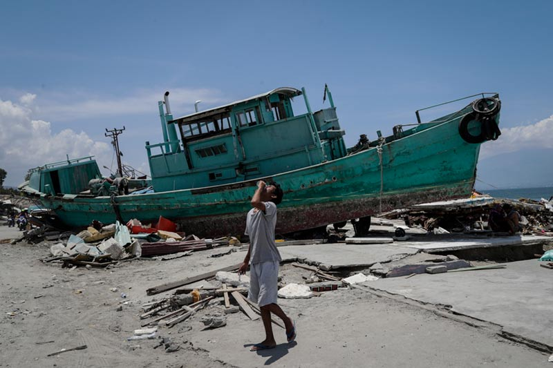 Boy by breached boat after Indonesian earthquake and tsunami