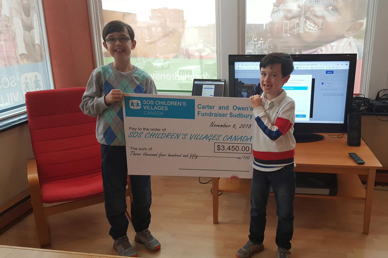 Young brothers presenting their fundraising cheque