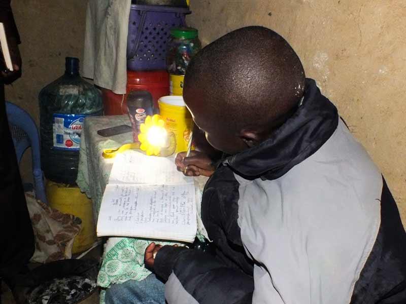 You girl doing homework at night using a sun lamp