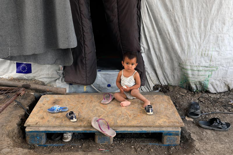 Boy sitting outside of a tent in the refugee camp in Lesvos, Greece